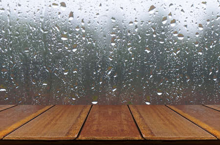 Rain Drops on Glass Window Background with Wood Table. Stock Photo