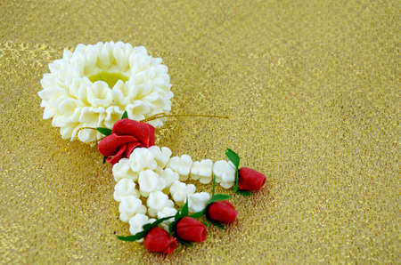 buddism: Thai Traditional Style Flowers Assortment on Golden Fabric Background.
