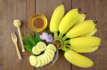 antiaging: Thai beauty and anti-aging dessert recipe. Cultivated Banana (Musa sapientum Linn.) with honey on Natural Wood Background. Stock Photo