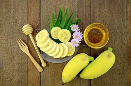 linn: Thai beauty and anti-aging dessert recipe. Cultivated Banana (Musa sapientum Linn.) with honey on Natural Wood Background. Stock Photo