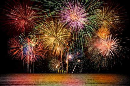 Colorful firework celebration on dark night sky background. Beautiful fireworks show on clear night sky. Stock Photo