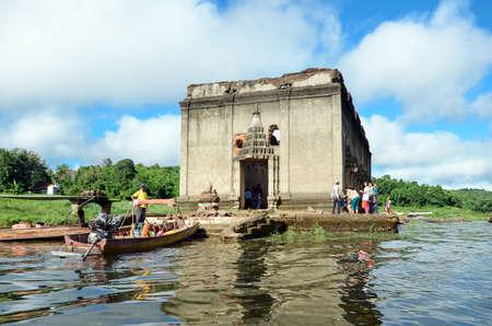 wiwekaram: OLD WAT WANG WIWEKARAM SAGKLABURI 12 OCT 2014:Tourists in a long tail boat at the entrance of The Sunken Temple, Wat Wang Wiwekaram, Kanchanaburi, Thailand.