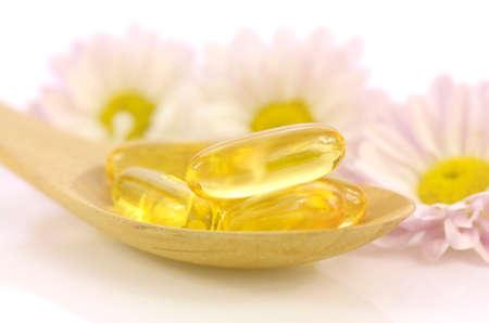 De zachte gelatinecapsules van dieetsupplement met chrysant bloeit achtergrond in het warme lichte toon vertegenwoordigde concept van de vrouwengezondheid.