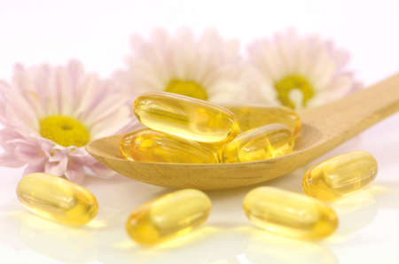 Soft gelatin capsules of dietary supplement with chrysanthemum flowers background in warm light tone represented women health concept.