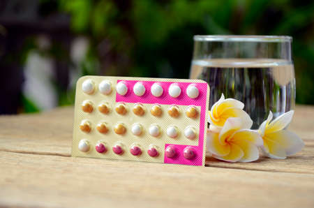 Oral contraceptive pills education wth triphasic pills regimen on natural green background.
