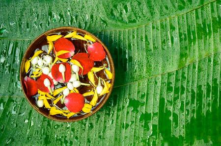 Bananenbladeren als achtergrond met hout blazen zich vol met geurig water, rozenblaadjes, goudsbloembloemblaadjes en jasmijnbloemen. Achtergrond van de het festival de Thaise stijl van Songkran.