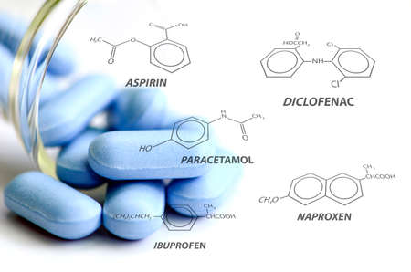 Blue caplets and some analgesic chemical structure on white background.