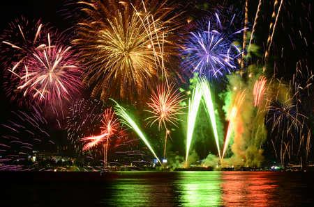 Colorful fireworks celebration and the city night light background. Banco de Imagens
