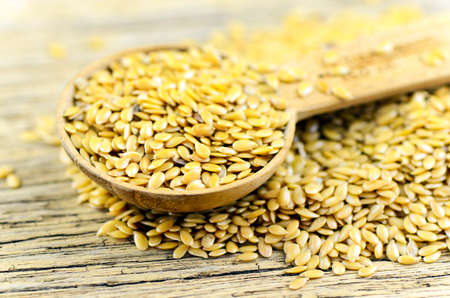 Spoonful of golden flax seed on wood background.