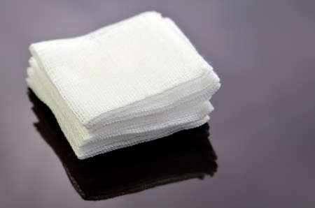 Stack of sterile gauze pad on dark background. Foto de archivo