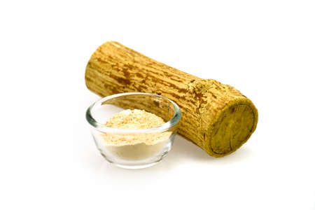 Thanaka wood and a cup of yellowish-white powder made from ground bark. Stock Photo