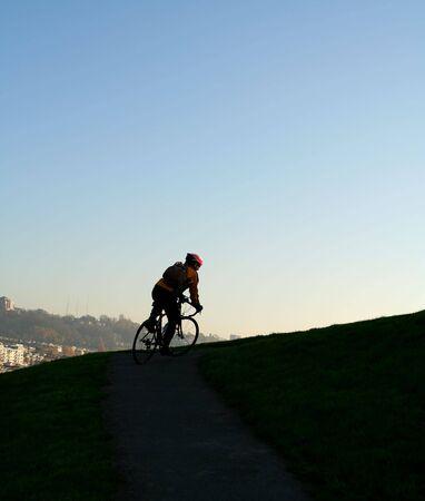 en mont�e: Un homme escalade mont�e sur un v�lo montrant l'effort et la d�termination  Banque d'images