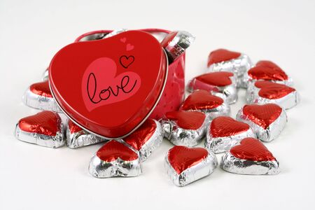 Heart-shaped box with heart-shaped chocolates Imagens