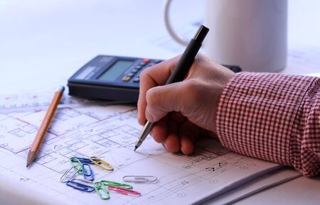 Working on a house blueprint Stock Photo