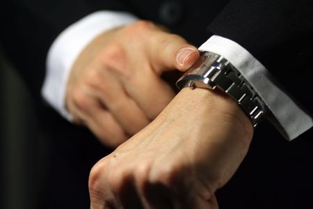 A businessman looking at his watch, deadlinedue theme