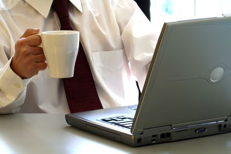hardworker: A businessman is drinking a cup of coffee and working on his laptop Stock Photo