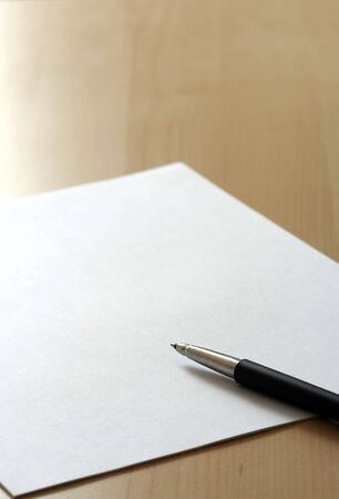 Blank white business paper and a pen on a table