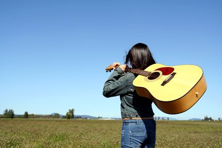 allurement: A woman holding a guitar looking at an empty field