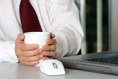 Businessman with a cup of coffee and laptop photo