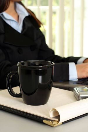 A businesswoman working in the office with a cup of coffee