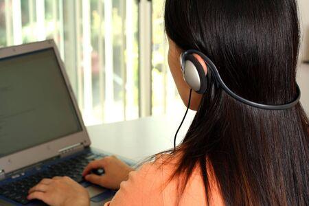 Een vrouw werkt op een laptop en het luisteren naar muziek met behulp van een hoofdtelefoon in een kantoor