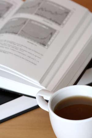 makelaardij: Een kopje koffie en een investering boek Stockfoto