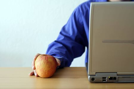 Businessman working on a laptop and holding an apple