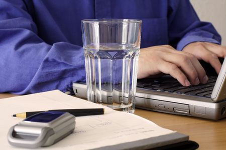 Businessman working on a laptop with a glass of water Stok Fotoğraf