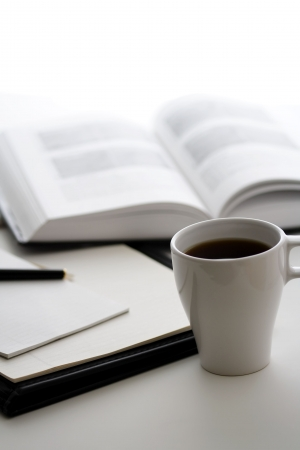 A cup of coffee, a book and a notepad
