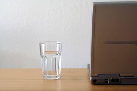 ノート パソコンと一杯の水