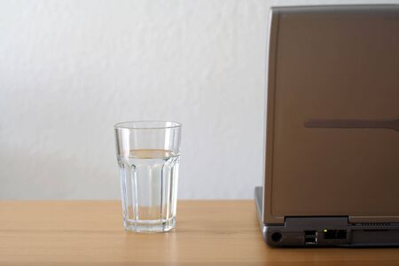 A laptop and a glass of water Imagens