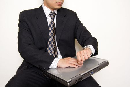 A businessman looking at his watch while holding a laptop, can be used for deadlinewaiting metaphor Stok Fotoğraf