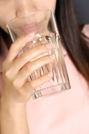 dehydration: A woman drinking a glass of water