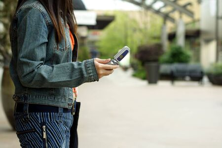 A woman with a cellphone in an outdoor shopping mall photo