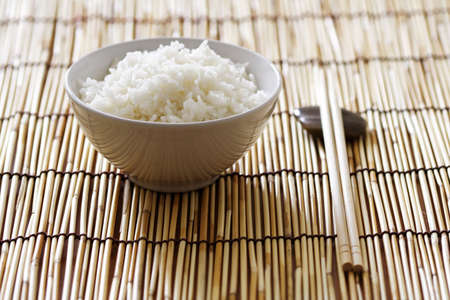 A bowl of rice and chopsticks