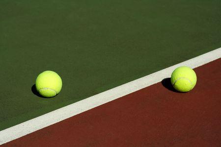 Two tennis balls in a tennis court