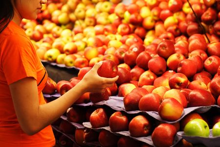 A woman shopping for apples at a grocery store photo