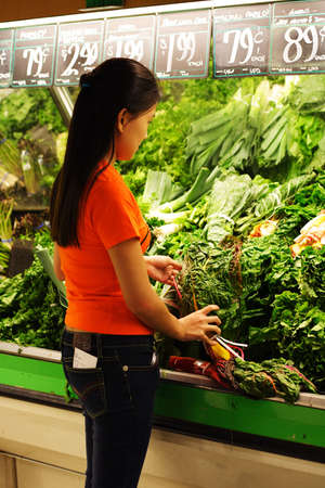 A woman shopping at produce section of grocery store Stock Photo