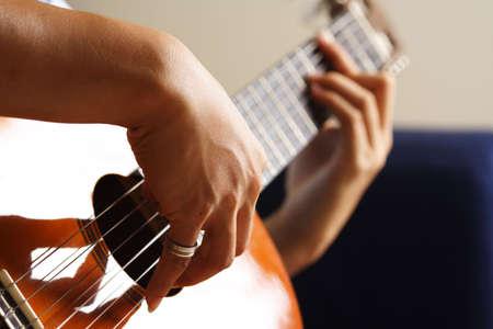 resonate: A close up shot of a strumming guitar player