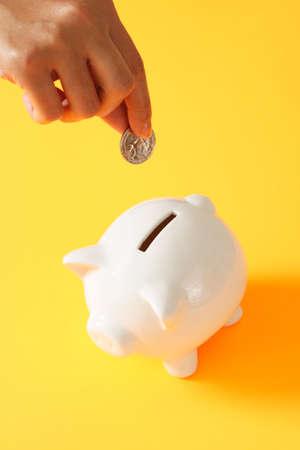 consolidate: A woman saving a coin into a piggy bank Stock Photo