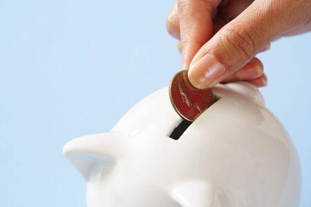 A woman saving a coin into a piggy bank Stock Photo