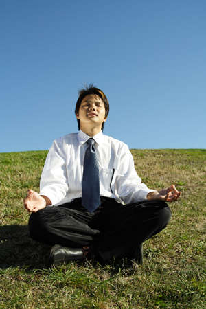 A businessman meditating in a park photo