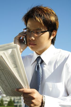 financial newspaper: Businessman reading a financial newspaper while making a phone call