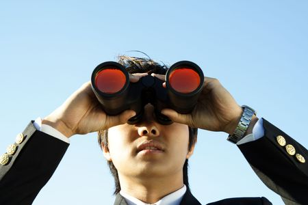 Businessman looking through binoculars, can be used for visionprospects metaphor photo