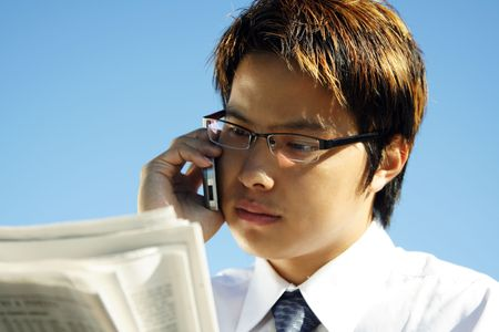 Businessman reading financial newspaper while making a phone call photo