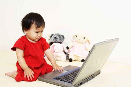 かわいい小さな女の赤ちゃんのラップトップで遊んで