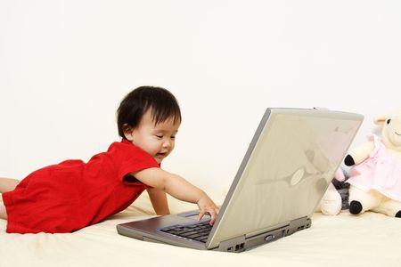 ノート パソコンで遊んでいるかわいい赤ちゃん女の子