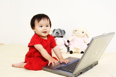 かわいい小さな女の赤ちゃんはラップトップで遊んで