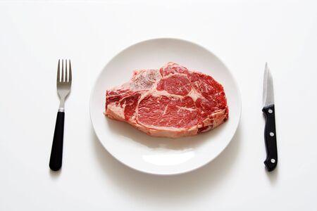 steak cru: Raw steak sur une plaque  Banque d'images