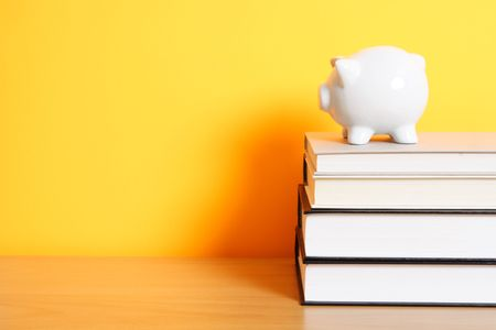 A piggy bank on top of a stack of books, good for saving for college theme Stock Photo - 515917